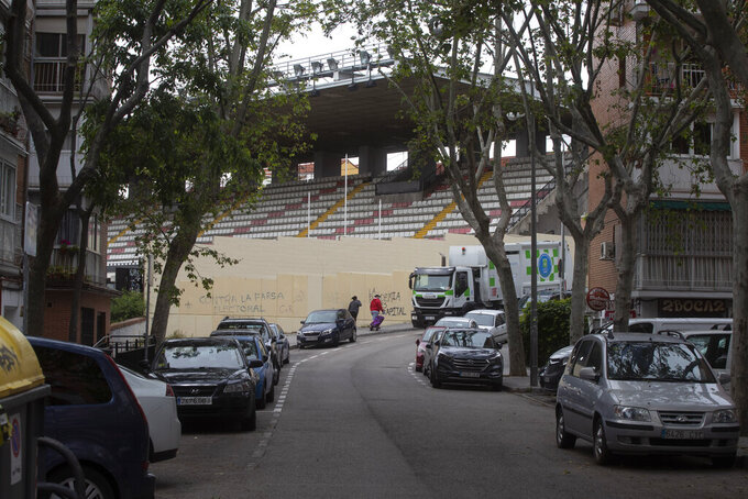 A couple walk past the closed stadium of Spanish 2nd division club Rayo Vallecano in Madrid, Spain, Thursday May 14, 2020. Soccer players in Spain are currently allowed to undergo individual training sessions at their team's training camps, with longer group sessions and full squad practices expected in the coming weeks if the coronavirus pandemic doesn't get worse. La Liga president Javier Tebas has said he hopes the league can restart on June 12.  (AP Photo/Paul White)