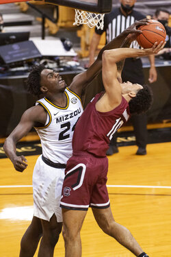 Missouri's Kobe Brown, left, blocks the shot of South Carolina's Justin Minaya during the first half of an NCAA college basketball game Tuesday, Jan. 19, 2021, in Columbia, Mo. (AP Photo/L.G. Patterson)