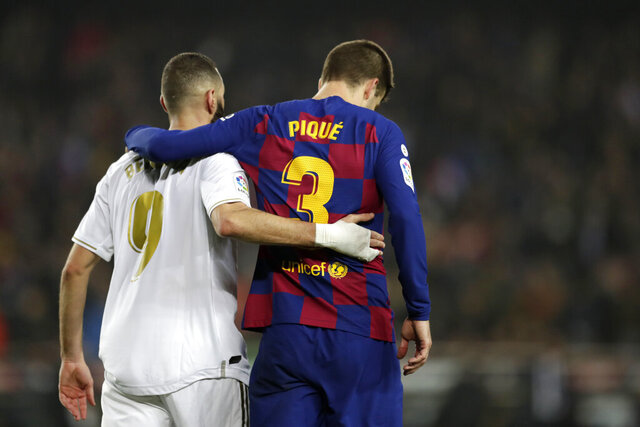 Real Madrid's Karim Benzema, left, and Barcelona's Gerard Pique walks together on the pitch during a Spanish La Liga soccer match between Barcelona and Real Madrid at Camp Nou stadium in Barcelona, Spain, Wednesday, Dec. 18, 2019. Thousands of Catalan separatists are planning to protest around and inside Barcelona's Camp Nou Stadium during Wednesday's
