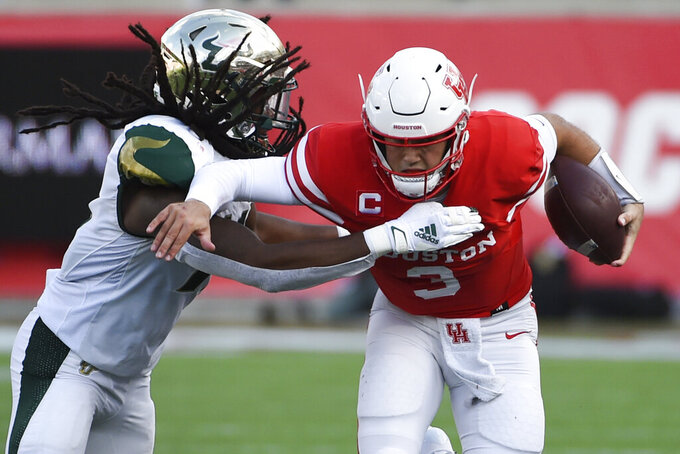 Houston quarterback Clayton Tune (3) is tackled by South Florida linebacker Dwayne Boyles during the first half of an NCAA college football game, Saturday, Nov. 14, 2020, in Houston. (AP Photo/Eric Christian Smith)