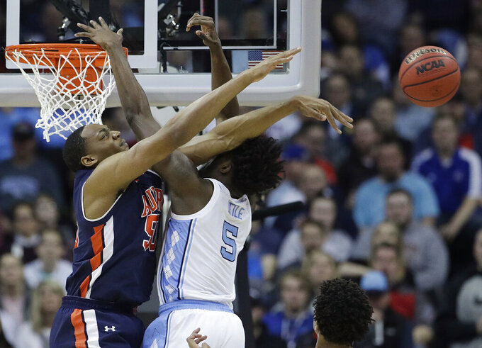 Auburn's Austin Wiley, left, knocks the ball away from North Carolina's Nassir Little (5) during the second half of a men's NCAA tournament college basketball Midwest Regional semifinal game Friday, March 29, 2019, in Kansas City, Mo. (AP Photo/Charlie Riedel)