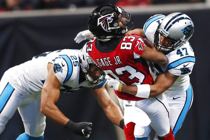 Carolina Panthers' Eric Reid (25) and Ross Cockrell (47) tackle Atlanta Falcons wide receiver Russell Gage (83) during the first half of an NFL football game, Sunday, Dec. 8, 2019, in Atlanta. (AP Photo/John Bazemore)