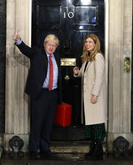 "FILE - In this file photo dated Friday, Dec. 13, 2019, Britain's Prime Minister Boris Johnson stands with his partner Carrie Symonds, on the steps of the Prime Minister's official residence 10 Downing Street in London. Expectations for the coming 2020 year are high, fuelled by Johnson's upbeat approach and his New Year's message saying Britain ""can start a new chapter in the history of our country, in which we come together and move forward united, unleashing the enormous potential of the British people."" (AP Photo/Matt Dunham, FILE)"