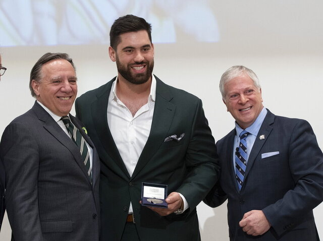 FILE - In this Feb. 18, 2020, file photo, Kansas City Chiefs' Laurent Duvernay-Tardif, center, receives the National Assembly of Quebec Medal of Honour from Speaker Francois Paradis, right, while Quebec Premier Francois Legault, left, looks on at the legislature in Quebec City, Quebec. Duvernay-Tardif has gone from the offensive line to the front line, using the medical degree he completed during offseasons with the Super Bowl champion Chiefs to help patients during the COVID-19 pandemic. (Jacques Boissinot/The Canadian Press via AP)