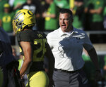 Oregon head football coach Mario Cristobal, right, yells encouragement to his team during warm ups before their NCAA college football game against California Saturday, Oct.. 5, 2019, in Eugene, Ore. (AP Photo/Chris Pietsch)