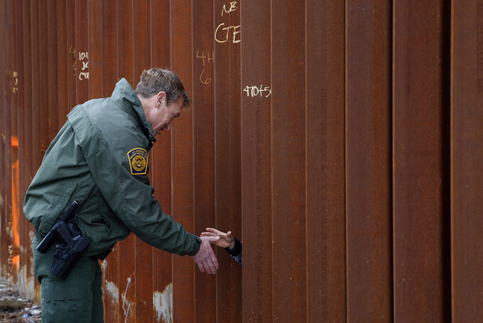 FILE - In this Jan 15, 2019, file photo, Rodney Scott, then-U.S. Border Patrol's San Diego sector chief shakes hands through a section of newly-replaced border wall in San Diego. The chief of the Border Patrol said Wednesday, June 23, 2021, he was leaving his job after less than two years in a position that lies in the crosshairs of polarizing political debate. Rodney Scott wrote to agents that he will be reassigned. (AP Photo/Gregory Bull, File)