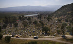 Graves are decorated with crosses and grass in a section of the municipal cemetery Valle de Chalco amid the new coronavirus pandemic, on the outskirts of Mexico City, Sunday, Oct. 25, 2020. Mexican families traditionally flock to local cemeteries to honor their dead relatives as part of the