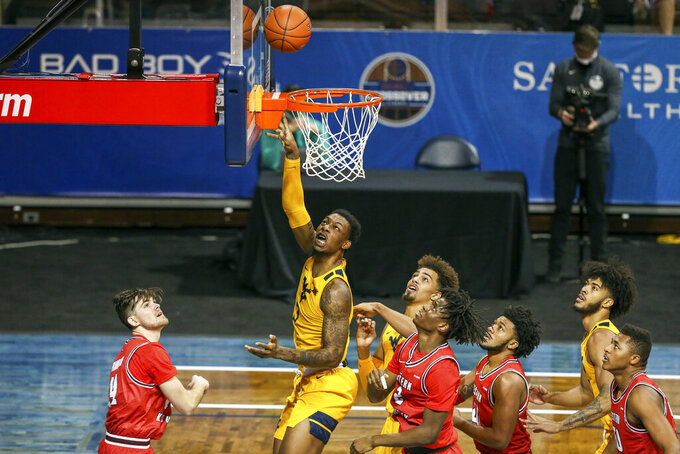 West Virginia forward Gabe Osabuohien (3) puts up a layup over several Western Kentucky defenders during the first half of an NCAA college basketball game Friday, Nov. 27, 2020, in SIoux Falls, S.D. (AP Photo/Josh Jurgens)