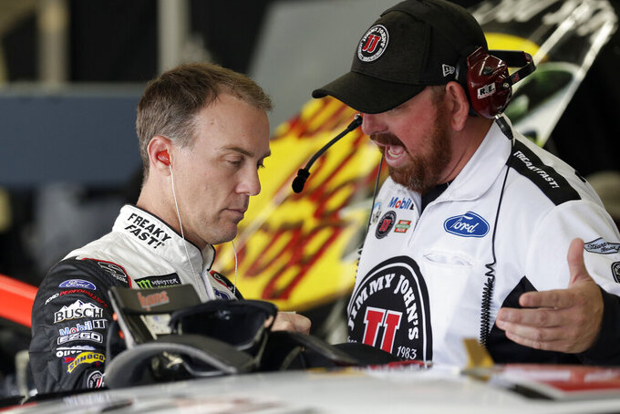 Kevin Harvick, left, speaks with a crew member in the garage during practice Sunday's NASCAR Cup Series auto race at Charlotte Motor Speedway in Concord, N.C., Saturday, Sept. 28, 2019. (AP Photo/Gerry Broome)