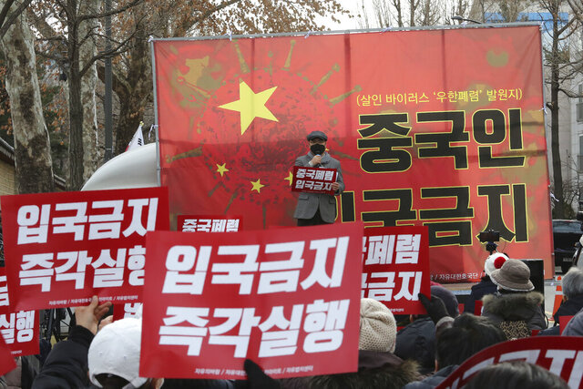 In this Wednesday, Jan. 29, 2020, photo, South Korean protesters stage a rally calling for a ban on Chinese people entering South Korea near the presidential Blue House in Seoul, South Korea. A scary new virus from China has spread around the world. So has rising anti-Chinese sentiment, calls for a full travel ban on Chinese visitors and indignities for Chinese and other Asians. The signs read: