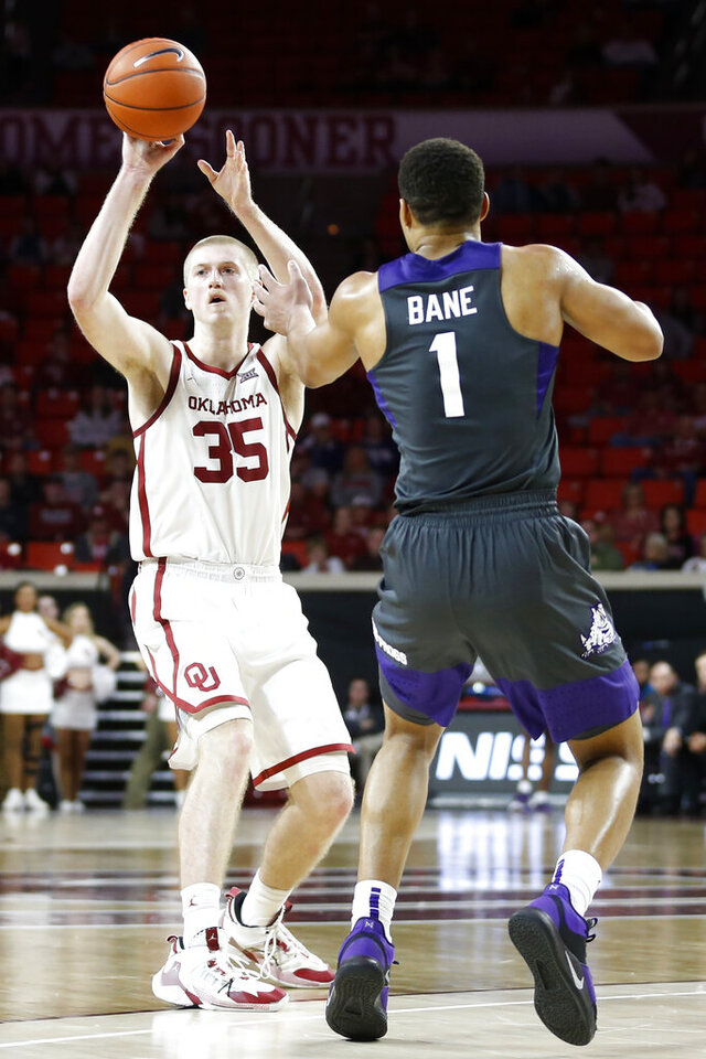 Oklahoma's Brady Manek (35) passes the ball as TCU's Desmond Bane (1) defends during the second half of an NCAA college basketball game in Norman, Okla., Saturday, Jan. 18, 2020. (AP Photo/Garett Fisbeck)