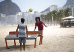 Two men play teqball amid the new coronavirus pandemic on Copacabana beach in Rio de Janeiro, Brazil, Thursday, July 2, 2020, as authorities begin to ease the city's lockdown against the growing COVID-19 pandemic. Teqball is played over a curved table combining elements of soccer and table tennis. (AP Photo/Silvia Izquierdo)