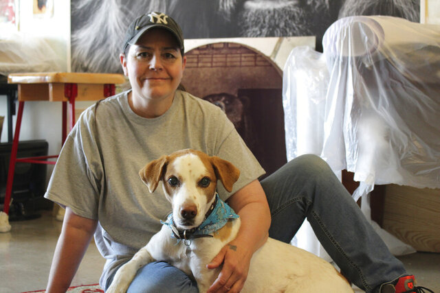 In this June 16, 2020 photo, Wendy Weiss Voeller and  her dog Buddy pose in Minot, N.D.  Art serves different purposes to each individual artist. It currently serves as a way for Wendy Weiss Voeller to raise money for her four-legged friend, Buddy, a Brittany mix that has glaucoma in both eyes, slowly causing him to go blind. (Ciara Parizek/Minot Daily News via AP)
