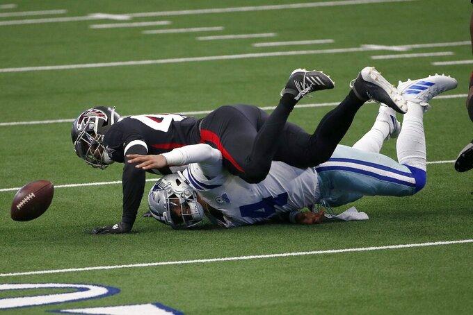 Dallas Cowboys quarterback Dak Prescott (4) fumbles the ball after being sacked by Atlanta Falcons linebacker Deion Jones, top, in the first half of an NFL football game in Arlington, Texas, Sunday, Sept. 20, 2020. (AP Photo/Ron Jenkins)