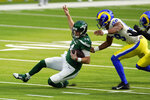 New York Jets quarterback Sam Darnold, left, slides in front of Los Angeles Rams linebacker Justin Hollins during the first half of an NFL football game Sunday, Dec. 20, 2020, in Inglewood, Calif. (AP Photo/Ashley Landis)