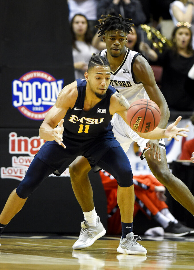 East Tennessee State Buccaneers forward Jeromy Rodriguez (11) tries to recover the ball in front of Wofford Terriers forward Chevez Goodwin (1) in the first half of a semifinal NCAA college basketball game for the Southern Conference tournament championship, Sunday, March 10, 2019, in Asheville, N.C. (AP Photo/Kathy Kmonicek)