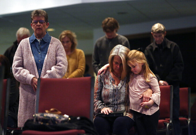 Angela Tucker hugs her 5-year-old granddaughter, Charley Jones, as they pray with their fellow congregants at Calvary of Neosho, a Southern Baptist church, Sunday, Nov. 22, 2020, in Neosho, Mo. Newton County, population 58,000, was recently hit by a surge of the coronavirus, with about 3,000 cases and 40 deaths in late November. (AP Photo/Jessie Wardarski)