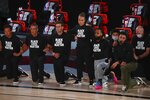 San Antonio Spurs assistant coach Becky Hammon stands as other players and staff kneel in Black Lives Matters shirts before a NBA basketball game against the Sacramento Kings Friday, July 31, 2020, in Lake Buena Vista, Fla. (Kim Klement/Pool Photo via AP)