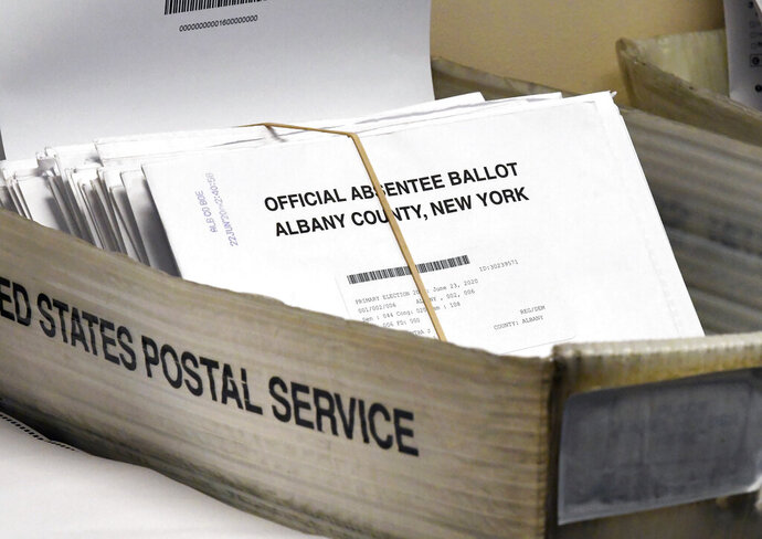 FILE - In this June 30, 2020, file photo, a box of absentee ballots wait to be counted at the Albany County Board of Elections in Albany, N.Y. A New York federal judge ordered the U.S. Postal Service to live up to its responsibilities to timely process election mail. The Monday, Sept. 21 written decision by Judge Victor Marrero came after several individuals including candidates for public office sued. (AP Photo/Hans Pennink, File)