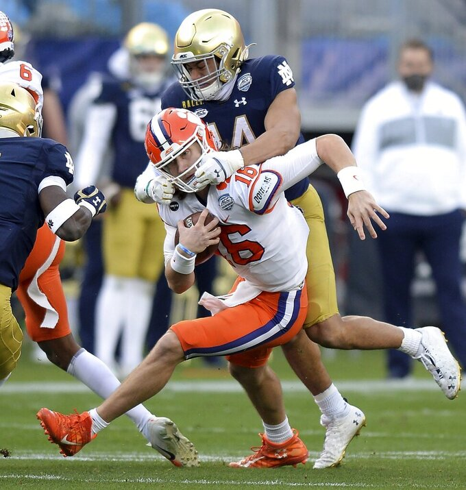 Notre Dame safety Kyle Hamilton grabs the face mask of Clemson quarterback Trevor Lawrenceduring the Atlantic Coast Conference championship NCAA college football game, Saturday, Dec. 19, 2020, in Charlotte, N.C. (Jeff Siner/The News & Observer via AP)