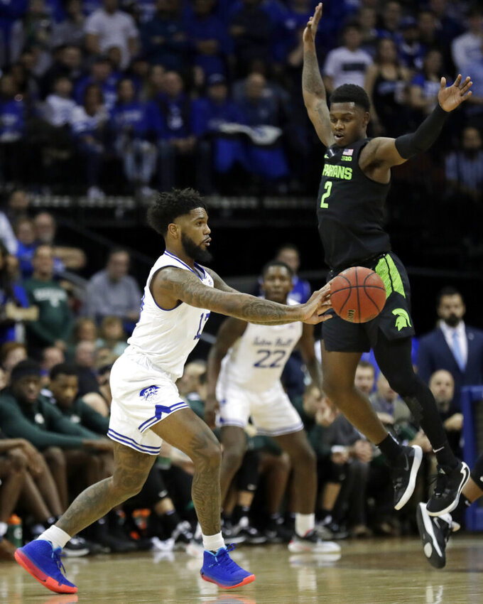 Seton Hall guard Myles Powell, left, passes around Michigan State guard Rocket Watts (2) during the first half of an NCAA college basketball game Thursday, Nov. 14, 2019, in Newark, N.J. (AP Photo/Adam Hunger)