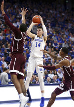 Kentucky's Tyler Herro (14) shoots between Texas A&M's Savion Flagg, left, and Wendell Mitchell, right, during the second half of an NCAA college basketball game in Lexington, Ky., Tuesday, Jan. 8, 2019. Kentucky won 85-74. (AP Photo/James Crisp)
