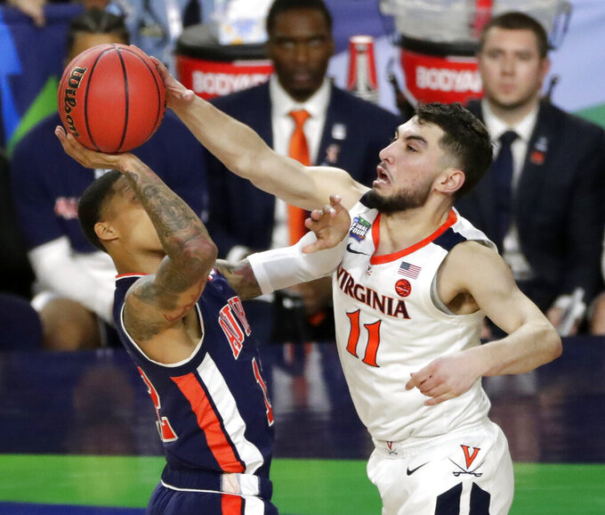 Virginia's Ty Jerome (11) blocks a shot by Auburn's J'Von McCormick (12) during the second half in the semifinals of the Final Four NCAA college basketball tournament, Saturday, April 6, 2019, in Minneapolis. (AP Photo/Matt York)