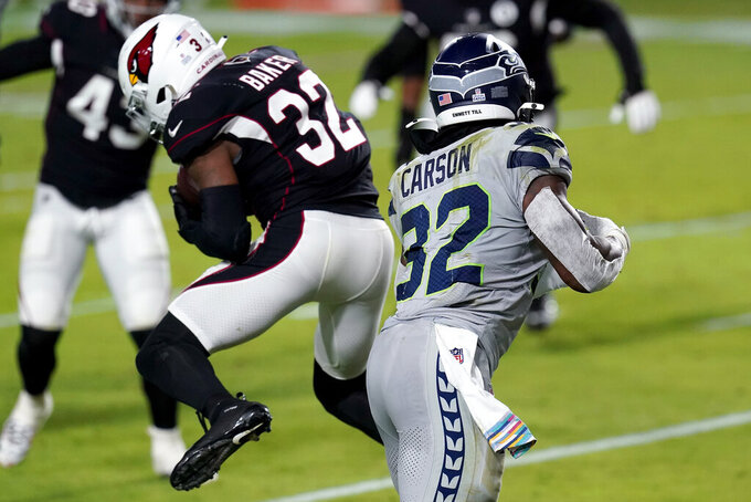 Arizona Cardinals strong safety Budda Baker, left, intercepts a pass intended for Seattle Seahawks running back Chris Carson, right, during the first half of an NFL football game, Sunday, Oct. 25, 2020, in Glendale, Ariz. (AP Photo/Ross D. Franklin)