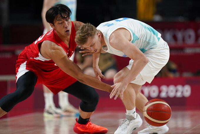 Japan's Tenketsu Harimoto (88), left, knocks the ball away from Slovenia's Luka Rupnik (5) during men's basketball preliminary round game at the 2020 Summer Olympics, Thursday, July 29, 2021, in Saitama, Japan. (AP Photo/Eric Gay)