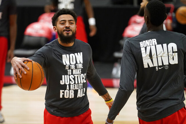 Toronto Raptors guard Jalen Harris, left, and forward Chris Boucher wear shirts honoring the late Rev. Martin Luther King during warmups before an NBA basketball game against the Charlotte Hornets Thursday, Jan. 14, 2021, in Tampa, Fla. (AP Photo/Chris O'Meara)