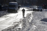 A man walks down an icy street in Madrid, Spain, Tuesday, Jan. 12, 2021. Schools remain closed in Madrid and many other parts of central Spain, with authorities focusing on reopening roads and stocking up supermarkets, struggling with the largest snowfall in half a century and record-low temperatures. (AP Photo/Paul White)