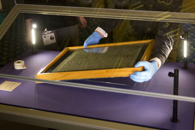 "FILE - In this Thursday, Feb. 5, 2015 file photo, the Salisbury Cathedral 1215 copy of the Magna Carta is installed in a glass display cabinet marking the 800th anniversary of the sealing of Magna Carta at Runnymede in 1215, in Salisbury, England. A judge has on Friday, July 10, 2020 sentenced a man to four years for attempting to steal Salisbury Cathedral's Magna Carta. Salisbury Crown Court Judge Richard Parkes sentenced Mark Royden, describing the failed theft as a ""determined attempt on a document of huge historical importance. (AP Photo/Matt Dunham, FILE)"