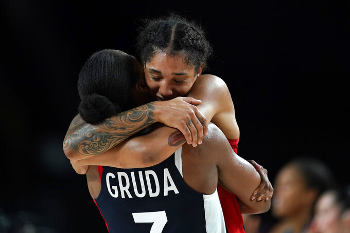 France's Gabrielle Williams gets a hug from teammate Sandrine Gruda at the end of the women's basketball bronze medal game against Serbia at the 2020 Summer Olympics, Saturday, Aug. 7, 2021, in Saitama, Japan. (AP Photo/Charlie Neibergall)