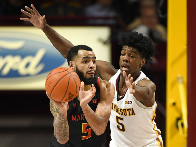 Maryland's Eric Ayala, left, passes the ball away from Minnesota's Marcus Carr during the first half of an NCAA college basketball game Wednesday, Feb. 26, 2020, in Minneapolis. (AP Photo/Hannah Foslien)