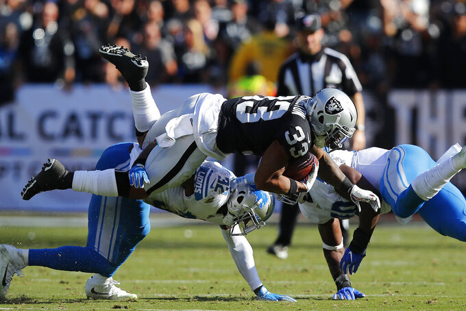 Oakland Raiders running back DeAndre Washington (33) is tackled by Detroit Lions defensive back Tavon Wilson (32) and middle linebacker Jarrad Davis during the first half of an NFL football game in Oakland, Calif., Sunday, Nov. 3, 2019. (AP Photo/John Hefti)