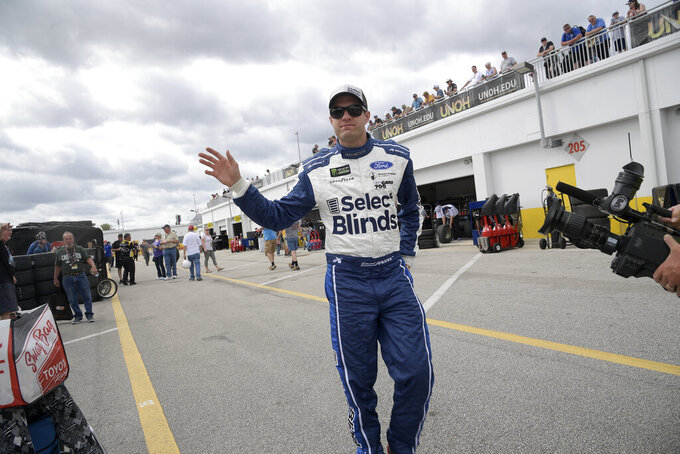 Driver David Ragan waves to fans while walking through the garage area during a practice session for the NASCAR Daytona 500 auto race at Daytona International Speedway Saturday, Feb. 16, 2019, in Daytona Beach, Fla. (AP Photo/Phelan M. Ebenhack)