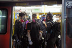 Protesters take a MTR train at the Yuen Long station in Hong Kong, Wednesday, Aug. 21, 2019. Hong Kong riot police faced off briefly with protesters occupying a suburban train station Wednesday evening following a commemoration of a violent attack there by masked assailants on supporters of the anti-government movement. (AP Photo/Kin Cheung)