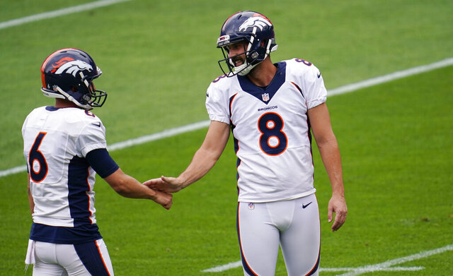 Denver Broncos punter Sam Martin, left, slaps hands with placekicker Brandon McManus as they take part in drills during an NFL football practice in empty Empower Field at Mile High, Saturday, Aug. 29, 2020, in Denver. (AP Photo/David Zalubowski)