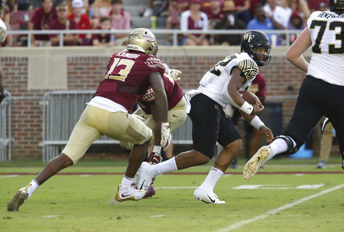 Wake Forest's quarterback Jamie Newman runs from pressure applied by Florida State's Joshua Kaindoh in the fourth quarter of an NCAA college football game, Saturday, Oct. 20, 2018 in Tallahassee, Fla. Florida State won 38-17. (AP Photo/Steve Cannon)
