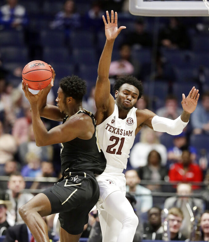 Vanderbilt forward Clevon Brown, left, grabs a rebound in front of Texas A&M forward Christian Mekowulu (21) in the first half of an NCAA college basketball game at the Southeastern Conference tournament, Wednesday, March 13, 2019, in Nashville, Tenn. (AP Photo/Mark Humphrey)