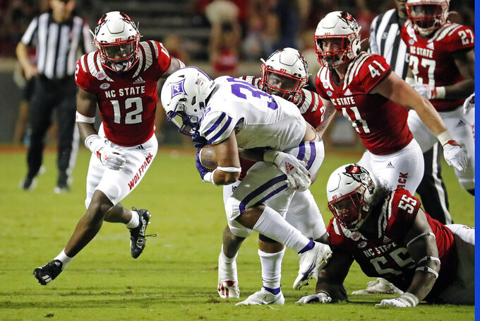 Furman's Jeff McElveen (35) is tied up by North Carolina State's Devon Betty (26) with State's Devan Boykin (12), Caden Fordham (41) and Joshua Harris (55) nearby during the second half of an NCAA college football game in Raleigh, N.C., Saturday, Sept. 18, 2021. (AP Photo/Karl B DeBlaker)