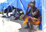 A woman covers her face at a camp for displaced survivors of cyclone Idai in Beira, Mozambique, Tuesday, April, 2, 2019.  Mozambican and international health workers raced Monday to contain a cholera outbreak in the cyclone-hit city of Beira and surrounding areas, where the number of cases has jumped to more than 1,000. (AP Photo/Tsvangirayi Mukwazhi)