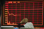 An investor monitors stock prices at a brokerage in Beijing on Thursday, Dec. 12, 2019. Asian shares are mixed after a wobbly day on Wall Street following the Federal Reserve announcement that it would leave interest rates unchanged. Japan's benchmark Nikkei 225, South Korea's Kospi and Hong Kong's Hang Seng rose in early Thursday trading. (AP Photo/Ng Han Guan)