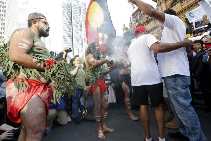Aboriginal men perform a smoking ceremony as protestors gather in Sydney, Saturday, June 6, 2020, to support the cause of U.S. protests over the death of George Floyd. Black Lives Matter protests across Australia proceeded mostly peacefully as thousands of demonstrators in state capitals honored the memory of George Floyd and protested the deaths of indigenous Australians in custody. (AP Photo/Rick Rycroft)