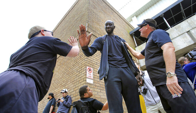 In this Wednesday, March 20, 2019 photo, Colt Kohler, 11, gets a high-five from Central Florida center Tacko Fall, as dad Erik Kohler looks on as UCF departs for the NCAA college basketball tournament in Orlando, Fla. Fall, at 7-foot-6 the tallest player in the game, at last gets to appear on the game's biggest stage when UCF opens the NCAA Tournament on the college basketball's biggest stage. (Joe Burbank/Orlando Sentinel via AP)