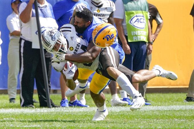 Pittsburgh defensive lineman Habakkuk Baldonado, right, loses his helmet as he tackles Western Michigan wide receiver Skyy Moore (24) during the first half of an NCAA college football game, Saturday, Sept. 18, 2021, in Pittsburgh. (AP Photo/Keith Srakocic)