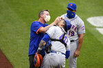 New York Mets catcher Wilson Ramos (40) gets tended to by a trainer as manager Luis Rojas (19) looks on during the sixth inning of the first baseball game of a doubleheader against the Washington Nationals, Saturday, Sept. 26, 2020, in Washington. The game is a makeup from Sept. 25. (AP Photo/Nick Wass)