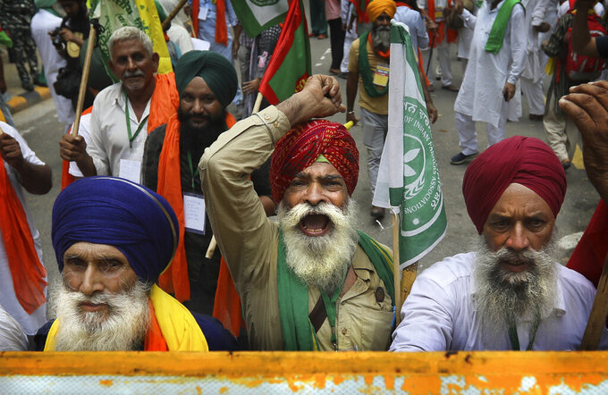 Farmers shout anti government slogans during a protest in New Delhi, India, Thursday, July 22, 2021. More than 200 farmers on Thursday began a protest near India's Parliament to mark eight months of their agitation against new agricultural laws that they say will devastate their income. (AP Photo/Manish Swarup)