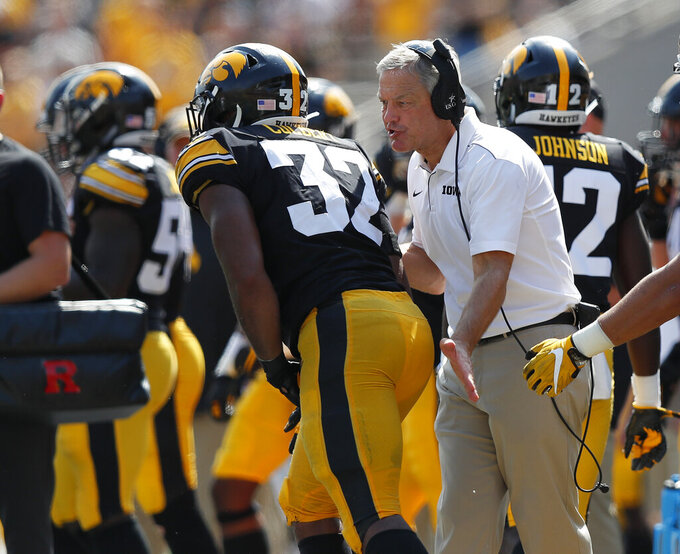 Iowa head coach Kirk Ferentz, right, talks with Iowa linebacker Djimon Colbert, left, after a play during the second half of an NCAA college football game against Rutgers, Saturday, Sept. 7, 2019, in Iowa City. Iowa won 30-0. (AP Photo/Matthew Putney)