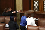 U.S. Capitol Police with guns drawn watch as rioters try to break into the House Chamber at the U.S. Capitol on Wednesday, Jan. 6, 2021, in Washington. (AP Photo/J. Scott Applewhite)